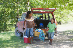 Father and son (8-10) unloading parked SUV on camping trip, sharing load of picnic hamper, smiling Stock Photography