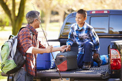 Father And Son Unpacking Truck On Camping Holiday. Looking At Each Other royalty free stock images