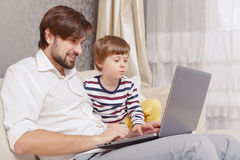 Father and son use computer Stock Images
