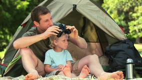 Father and son using binoculars stock video footage