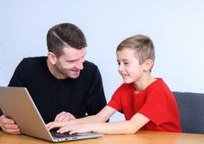 Father and son using computer together Stock Photos