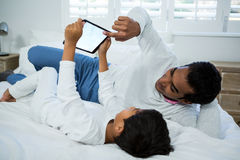Father and son using digital tablet on bed Royalty Free Stock Photos