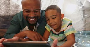 Father and son using digital tablet in bedroom 4k
