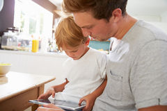 Father And Son Using Digital Tablet At Breakfast Table Stock Images