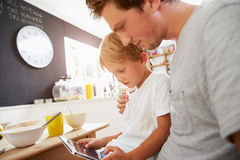Father And Son Using Digital Tablet At Breakfast Table Royalty Free Stock Photography