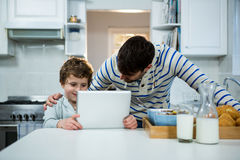 Father and son using digital tablet in the kitchen Stock Photo