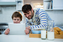 Father and son using digital tablet in the kitchen Royalty Free Stock Image