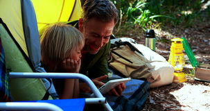 Father and son using digital tablet outside tent stock video