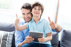 Father and son using digital tablet Stock Images