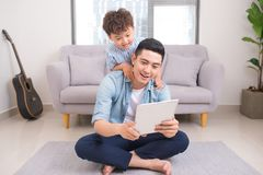 Father and son are using a digital tablet spending time together. At home Royalty Free Stock Photos