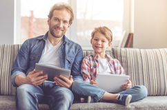 Father and son. Are using digital tablets and smiling while spending time together at home Stock Photos