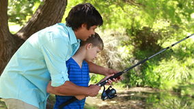 Father and son using a fishing rod together Royalty Free Stock Image
