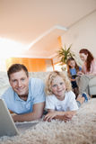Father and son using internet on the floor Royalty Free Stock Photography