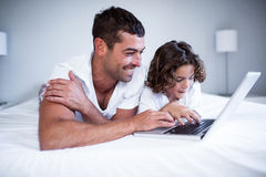 Father and son using laptop on bed Stock Images