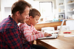 Father and son using laptop computer at home royalty free stock images