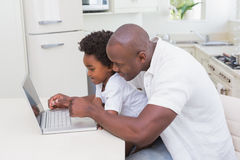 Father and son using laptop on the couch. At home in living room Royalty Free Stock Photos