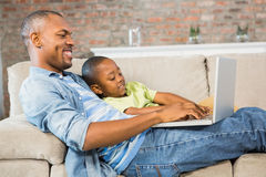 Father and son using laptop on the couch. In living room stock images