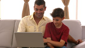 Father and son using laptop on the couch