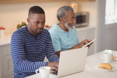 Father and son using laptop and digital tablet in kitchen. At home stock photos