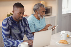 Father and son using laptop and digital tablet in kitchen. At home royalty free stock images