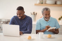 Father and son using laptop and digital tablet in kitchen. Smiling father and son using laptop and digital tablet in kitchen at home stock image