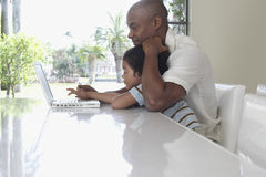 Father And Son Using Laptop At Dining Table Royalty Free Stock Photography