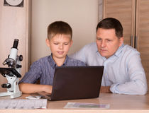 Father and son using laptop. Father helping his son doing school royalty free stock images