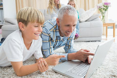 Father and son using laptop on the floor Stock Photo