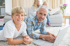 Father and son using laptop on the floor Stock Images