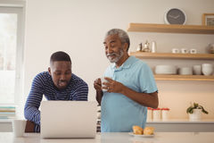 Father and son using laptop while having coffee in kitchen. Smiling father and son using laptop while having coffee in kitchen stock photos