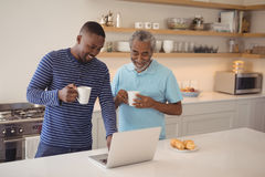 Father and son using laptop while having coffee in kitchen. Smiling father and son using laptop while having coffee in kitchen stock photography