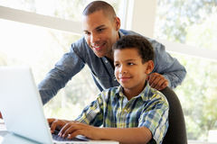 Father And Son Using Laptop At Home Stock Image