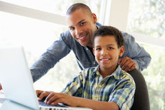 Father And Son Using Laptop At Home Stock Photos