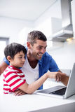 Father and son using laptop in kitchen. At home stock photo