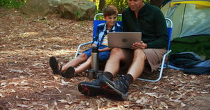 Father and son using laptop outside tent stock video footage