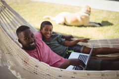 Father and son using laptop while relaxing on hammock Royalty Free Stock Photography