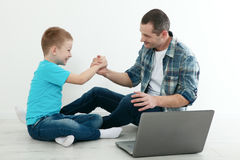 Father and son using laptop sitting on the hardwood floor togeth Royalty Free Stock Photos