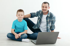 Father and son using laptop sitting on the hardwood floor togeth Royalty Free Stock Image