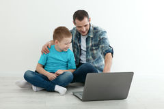 Father and son using laptop sitting on the hardwood floor togeth Royalty Free Stock Photography