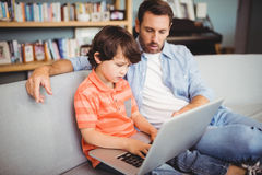 Father and son using laptop while sitting on sofa. At home Royalty Free Stock Images