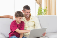 Father and son using laptop on sofa. Happy father and son using laptop while sitting on sofa at home Stock Image