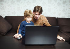 Father and son using laptop on sofa Stock Photos