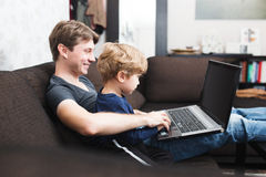 Father and son using laptop on sofa Royalty Free Stock Image
