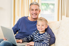 Father and son using laptop on the sofa. In living room Stock Image