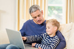 Father and son using laptop on the sofa. In living room Royalty Free Stock Photography