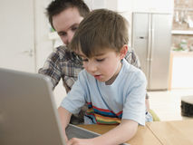 Father And Son Using Laptop At Table Royalty Free Stock Photos
