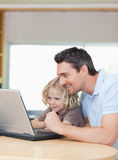 Father and son using laptop together. Smiling father and son using laptop together stock images