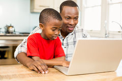 Father and son using laptop together. Happy couple using tablet and having breakfast in the kitchen royalty free stock photography