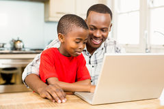 Father and son using laptop together. In the kitchen royalty free stock photo