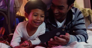 Father and son using mobile phone. In the bedroom 4k stock footage
